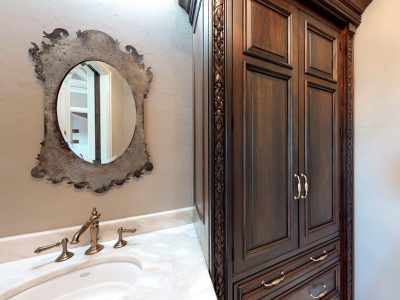 European Estate Her Powder Room is replete with a Linen Armoire, made-to-order and detailed with raised panel mahogany doors & woodcarvings in a laurel motif
