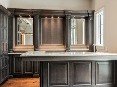 European Estate Wet Bar Stately maple woodwork is stained a striking shade of slate (warm purple gray) and conceals professional grade refrigeration